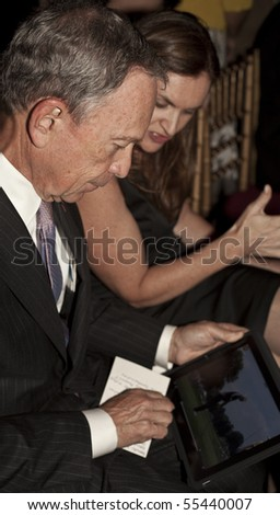 NEW YORK - JUNE 17: Mayor Michael Bloomberg checks iPad while attends Inside Broadway 2010 Beacon Awards at Players Club on June 17, 2010 in New York City. - stock photo