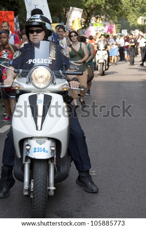 NEW YORK-JUNE 22: Police on motorcycles ride next to hundreds of supporters as they march in Lower Manhattan during the 8th Annual Trans Day of Action on June 22, 2012 in New York City.