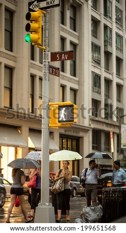 NEW YORK - JUNE 13: rainy day on Fifth Avenue on June 13, 2014 in New York. Fifth Avenue is a major thoroughfare that runs through Manhattan, New York City. - stock photo