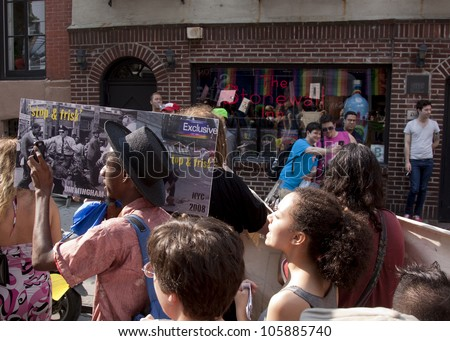 NEW YORK - JUNE 22: Supporters march past the legendary Stonewall Inn, known as the birthplace of the modern Gay Rights movement on the 8th Annual Trans Day of Action on June 22, 2012 in New York. - stock photo