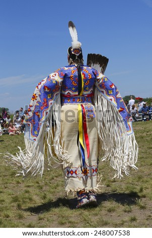 NEW YORK - JUNE 8, 2014: Unidentified female Native American dancer wears traditional Pow Wow dress during the NYC Pow Wow in Brooklyn - stock photo