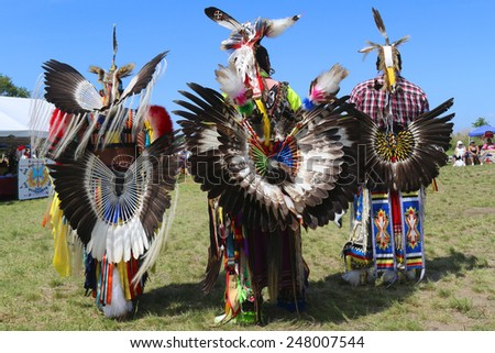 NEW YORK - JUNE 8, 2014: Unidentified male Native American dancers wears traditional Pow Wow dress with Dance Bustle during the NYC Pow Wow in Brooklyn - stock photo