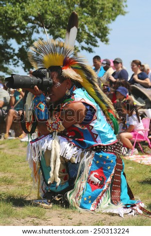 NEW YORK - JUNE 8, 2014: Unidentified Native American taking pictures at the NYC Pow Wow in Brooklyn. A pow-wow is a gathering and Heritage Celebration of North America s Native people