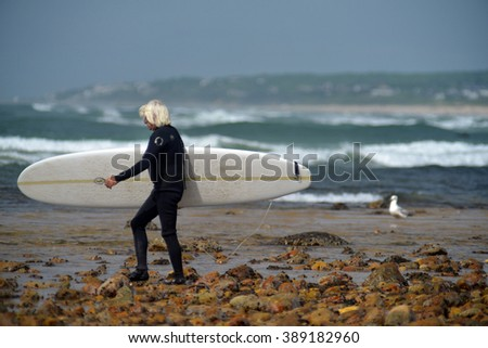NEW YORK-JUNE 13: Unidentified senior surfer with surfboard on Ditch Plains surfing beach Montauk, New York in the Hamptons on June 13, 2015.