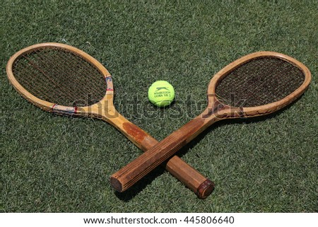 NEW YORK - JUNE 30, 2016:Vintage Tennis rackets and Slazenger Wimbledon Tennis Ball on grass tennis court. Slazenger Wimbledon Tennis Ball exclusively used and endorsed by The Championships, Wimbledon - stock photo