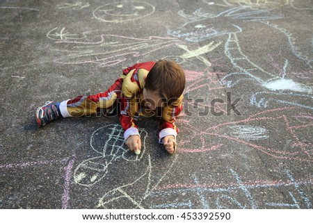 NEW YORK - JUNE 14, 2016: Young boy participates at chalk drawing during annual Museum Mile Festival in Manhattan. Kids and families draw with chalk on Fifth Avenue
