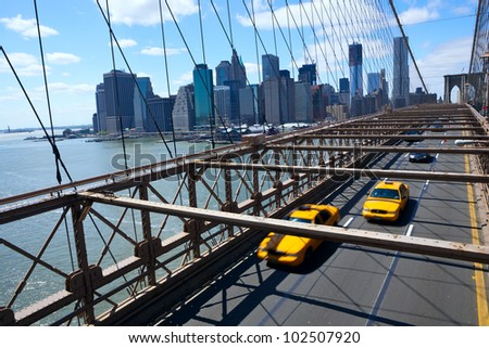 New York Manhattan skyline from the Brooklyn Bridge with yellow taxi's - stock photo