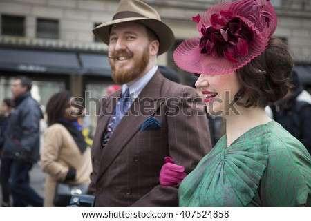 NEW YORK - MAR 27 2016: A couple dressed in fancy Easter outfits walk along 5th Avenue on Easter Sunday during the traditional Easter Bonnet Parade in Manhattan on March 27, 2016.