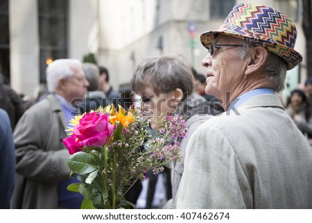 NEW YORK - MAR 27 2016: A man wearing a colorful straw hat holds a bouquet of flowers on Easter Sunday during the traditional Easter Bonnet Parade along 5th Ave in Manhattan on March 27, 2016. - stock photo