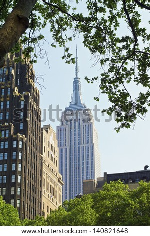 NEW YORK - MAY 21: A framed view of The Empire State Building from Bryant Park on May 21 2013 in Manhattan. The Empire State Building is currently the third tallest completed skyscraper in the US. - stock photo