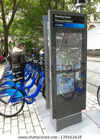 NEW YORK - MAY 24: A man looks at bicycles docked at a Citibike sharing kiosk at Bowling Green Station on May 24, 2013 in New York. Operated by NYC Bike Share, thousands of bikes will be available. - stock photo
