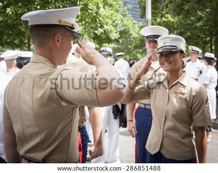 NEW YORK - MAY 22 2015: A US Marine Corpsman receives a salute from a fellow Marine after the promotion ceremony at the National September 11 Memorial site during Fleet Week 2015. - stock photo