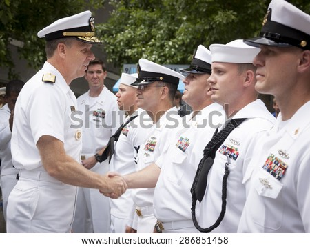 NEW YORK - MAY 22 2015: Admiral Phil Davidson shakes the hand of a U.S. Navy sailor who took part in the re-enlistment and promotion ceremony at the National September 11 Memorial site. - stock photo