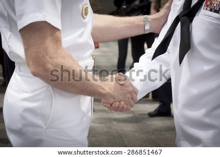 NEW YORK - MAY 22 2015: Close up of Admiral Phil Davidson shaking the hand of a U.S. Navy sailor who took part in the re-enlistment and promotion ceremony at the National September 11 Memorial site.