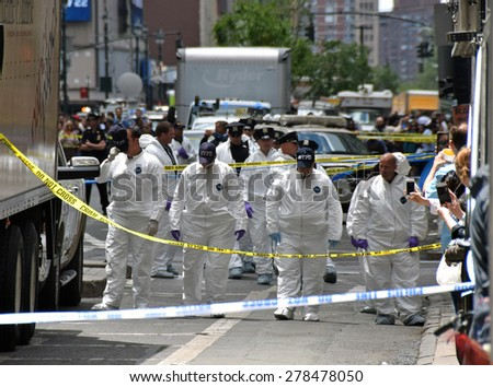 NEW YORK - MAY 13: Crime scene investigator scour the scene of a street shooting in New York City on May 13, 2015. The fatal shooting involved police and an armed man - stock photo