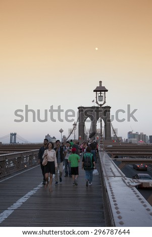 NEW YORK - May 30, 2015: People walking across the Brooklyn Bridge in New York city. Completed in 1883, it connects the boroughs of Manhattan and Brooklyn by spanning the East River.  - stock photo