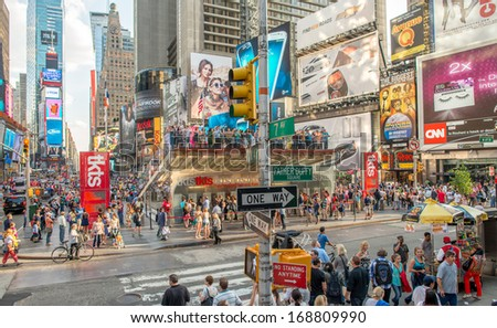 NEW YORK - MAY 22: Tourists walk in busy Times Square intersection, May 22, 2013 in New York City.Times Square is the most visited tourist attraction in the world with over 39 million visitors annually - stock photo