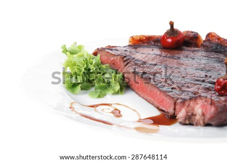 new york meat style beef steak fillet on white plate with hot chili pepper and green salad isolated over white background with stainless steel cutlery - stock photo
