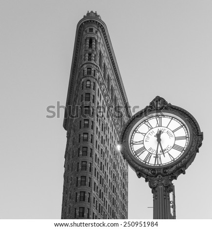 NEW YORK, NEW YORK - JANUARY 31, 2015: Flatiron Buliding and Fifth Avenue Clock. Completed in 1902, it is considered to be one of the first skyscrapers ever built. - stock photo