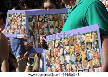 NEW YORK, NEW YORK - JULY 26, 2016: Gay Pride Parade participants holding up posters that feature images of the 49 victims of the Orlando shooting at Pulse nightclub. Editorial use only.  - stock photo