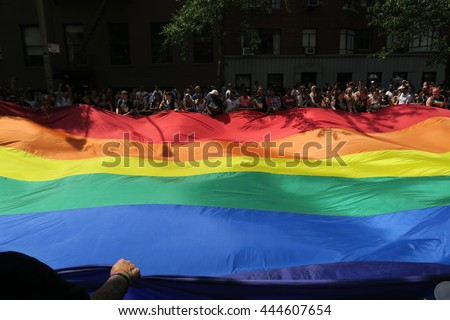 NEW YORK, NEW YORK - JULY 26, 2016: Giant rainbow flay in the Gay Pride Parade on 5th avenue. It is the symbol of lesbian, gay, bisexual and transgender (LGBT) pride and diversity. Editorial use only. - stock photo
