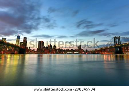 New York, New York - July 4, 2015: View of the Brooklyn Bridge and Manhattan Bridge at sunset from Brooklyn Bridge Park, New York. - stock photo
