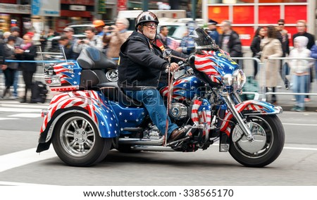 New York, New York - November 11, 2015: Biker rides up 5th Avenue during the Veterans Day Parade in New York City in 2015. - stock photo