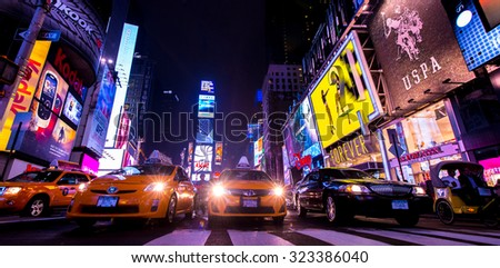 NEW YORK, NEW YORK - OCTOBER 5, 2013: Taxi's, pedicabs and livery car at a stop light in a crowded Times Square on October 5, 2013.  New York City is home to over 10 million people. - stock photo
