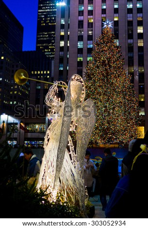 New York, New York, USA - December 19, 2005: An evening shot of the Rockefeller Center Christmas Tree and one of the white illuminated angels during the Christmas holiday season. - stock photo