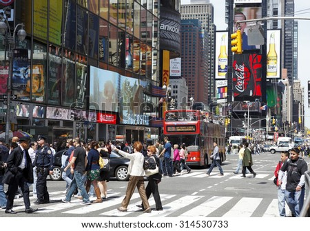 New York, New York, USA - May 1, 2011: Times Square photographed from 44th street looking uptown or north. People can be seen crossing 7th avenue with the colorful signage backdrop of Times Square.