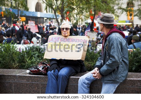 New York, New York, USA - November 3, 2011: A man and woman sit on a wall at Zuccotti Park. The woman is holding a sign with a message. Crowds of people can be seen in the background. Occupy Wall St. - stock photo