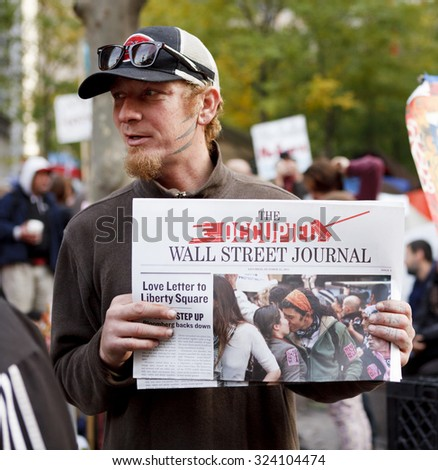 New York, New York, USA - November 3, 2011: A man holds up literature from the Occupy Wall Street movement at Zuccotti Park. Crowds of people can be seen in the background. - stock photo
