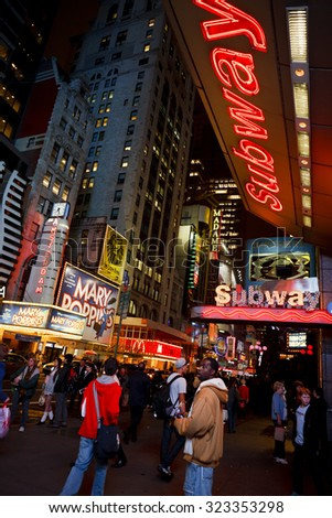 New York, New York, USA - October 13, 2011: Subway Stop on 42nd Street at night. The bright lights of 42nd street highlight the many entertainment options. Pedestrians can be seen. - stock photo