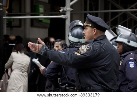 NEW YORK - NOV 17:  A police officer directs traffic on Broadway at Wall St near the entrance to the New York Stock Exchange on the 'Day of Disruption' on November 17, 2011 in New York City, NY. - stock photo