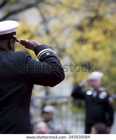 NEW YORK - NOV 25 2015: A U.S. Navy officer on a parade float salutes a sailor in the stands during the annual Americas Parade up 5th Avenue on Veterans Day in Manhattan. - stock photo