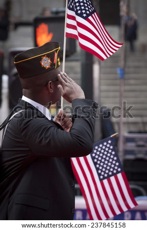 NEW YORK - NOV 11, 2014: A vet carrying an American Flag salutes as he marches past the VIP stage during the 2014 America's Parade held on Veterans Day in New York City on November 11, 2014. - stock photo