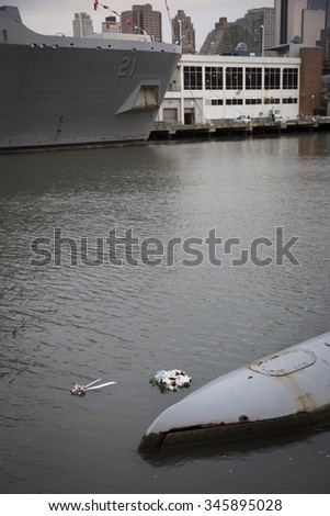NEW YORK - NOV 25 2015: A wreath floats between the USS New York (LPD-21) an amphibious transport dock and the USS Growler (SSG-577) submarine after the wreath laying ceremony on Veterans Day. - stock photo