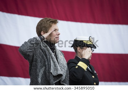 NEW YORK - NOV 25 2015: Army vet Loree Sutton Commissioner of NYC Office of Veterans Affairs and Rear Admiral Cynthia M. Thebaud salute for the presentation of colors on the Intrepid on Veterans Day. - stock photo