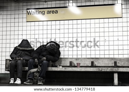NEW YORK - NOV 14: People sitting on a bench at a subway station's waiting area, hidden behind their coats, on November 14 2012 in New York, New York. - stock photo