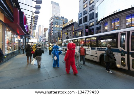 NEW YORK - NOV 6: Two actors hidden in Elmo and Cookie Monster costumes amuse the pedestrian walking by at 42nd street, just by Times Square in Manhattan  on November 6 2012 in New York, New York.
