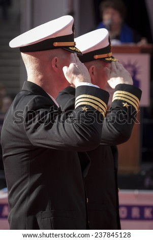 NEW YORK - NOV 11, 2014: Two commanders from the US Navy salute as they march past the VIP stage during the 2014 America's Parade held on Veterans Day in New York City on November 11, 2014. - stock photo