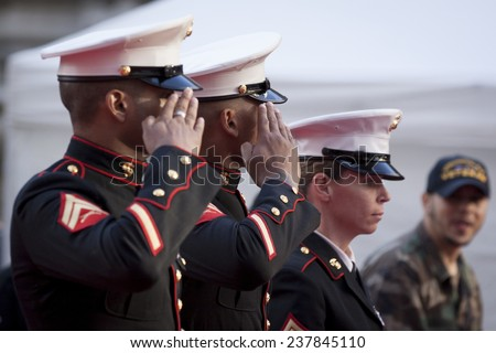 NEW YORK - NOV 11, 2014: Two US Marines salute as they march past the VIP stage during the 2014 America's Parade held on Veterans Day in New York City on November 11, 2014. - stock photo