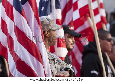 NEW YORK - NOV 11, 2014: US vets carry American Flags as they march in the 2014 America's Parade held on Veterans Day in New York City on November 11, 2014. - stock photo