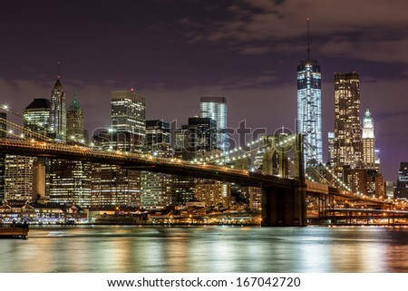 NEW YORK - NOVEMBER 2: Brooklyn Bridge and Manhattan skyline at night on November 2, 2013. Brooklyn Bridge connects Manhattan with Brooklyn and is one of the most famous landmarks in New York City.  - stock photo