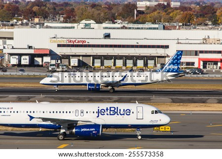 NEW YORK - NOVEMBER 3: JetBlue Embraer 190 and Airbus A320 taxi at JFK in New York, NY on November 3, 2013. JetBlue is New York based, fastest growing airline in the world. - stock photo