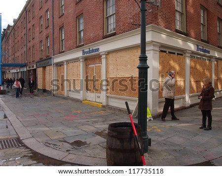 NEW YORK, NOVEMBER 3: Plywood covers storefronts at the South Street Seaport in New York City, November 3, 2012. Lower Manhattan was seriously damaged by flooding from Hurricane Sandy. - stock photo