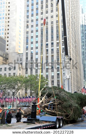 NEW YORK - NOVEMBER 12: The arrival and set up of the famous Rockefeller Center Christmas Tree in Rockefeller Center on November 12, 2010 in Manhattan, New York.  - stock photo