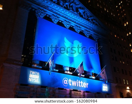 NEW YORK - NOVEMBER 7: The Twitter logo is shown in front of the NYSE on evening of its IPO on November 7, 2013 in New York. Twitter, ticker symbol: TWTR, went public today at $26 per share.  - stock photo