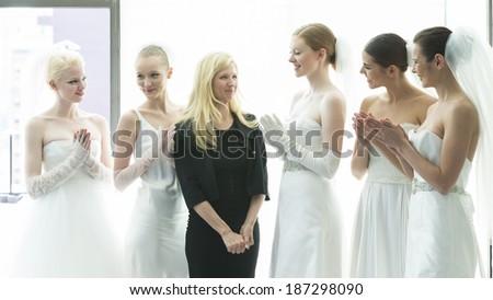 NEW YORK, NY - APRIL 11, 2014: Designer Justina McCaffrey and models pose during presentation of Jastina McCaffrey collection at bridal week at Penthouse Morgans hotel - stock photo