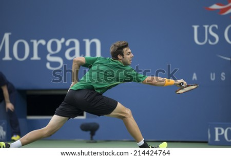 NEW YORK, NY - AUGUST 31, 2014: Marcel Granollers of Spain returns ball during 3rd round match against Roger Federer of Switzerland at US Open tennis tournament in Flushing Meadows USTA Tennis Center - stock photo